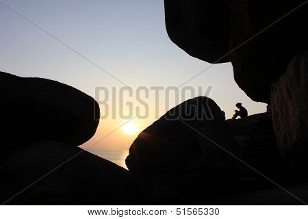 woman sitting as silhouette by the sea