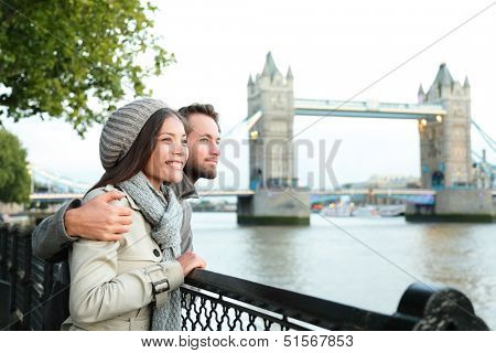 Happy couple by Tower Bridge, River Thames, London. Romantic young couple enjoying view during travel. Asian woman, Caucasian man in London, England, United Kingdom.