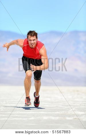 Running man - runner sprinting in desert nature. Fit athlete in fast sprint run at great speed towards camera. Male fitness model in amazing extreme desert landscape.
