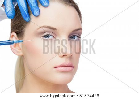 Attractive young model on white background having botox injection