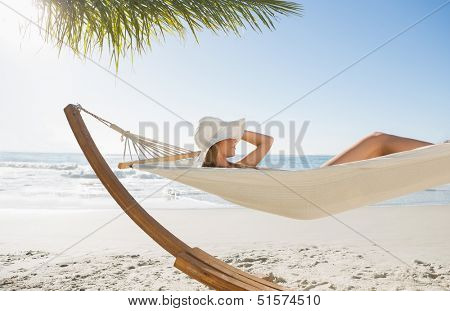 Woman wearing sunhat and bikini relaxing on hammock at the beach