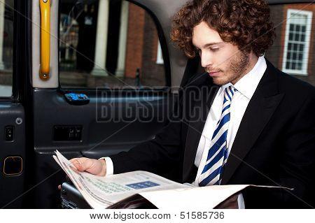 Businessman Reading Magazine Inside Taxi