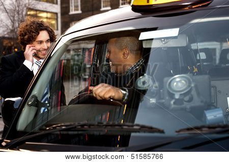Businessman Interacting With Taxi Driver