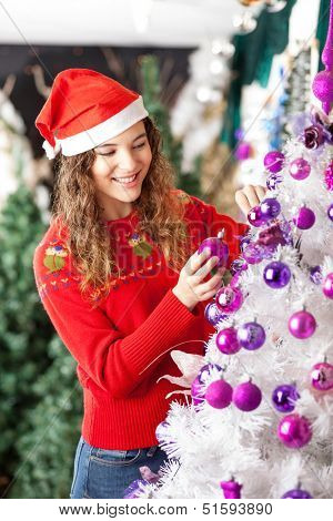 Happy female owner decorating Christmas tree at store
