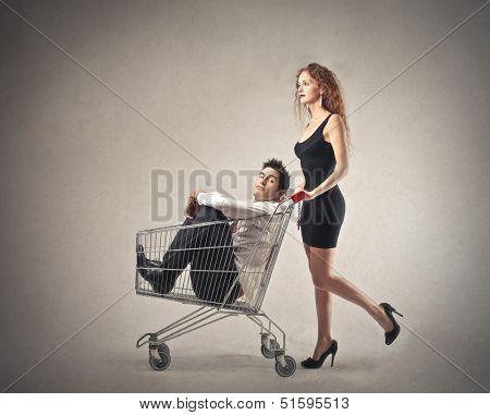 beautiful woman pushing shopping cart with businessman inside
