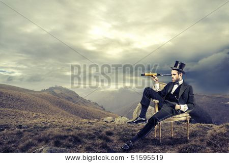 elegant man with cylinder looks through a telescope sitting on a chair in the mountain