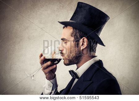 elegant man with cylinder drinking a glass of red wine