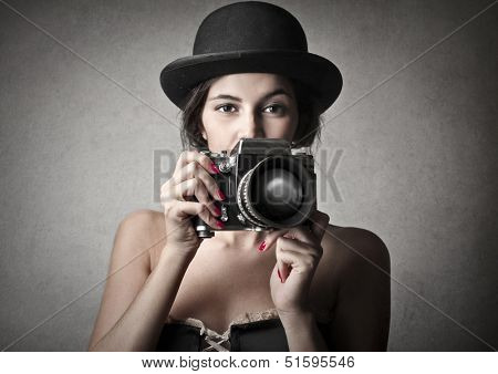 beautiful woman with bowler hat and vintage camera