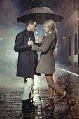 image of rainy season  - Elegant couple with umbrella on rainy evening - JPG