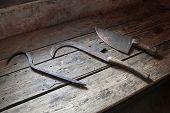 stock photo of torture  - Torturing equipment lay on wooden table in ancient castle - JPG