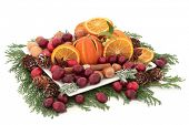 Christmas cranberry and dried orange fruit with nuts, spice and winter greenery over white backgroun