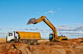 loader excavator machine loading dumper truck at sand quarry
