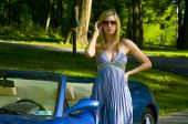 stock photo of beautiful woman  - an attractive blond woman posing in front of a blue convertible sports car - JPG