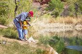foto of grandpa  - Grandpa fishing with his grandson at a beautiful lake - JPG