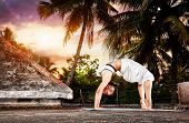 pic of dhanurasana  - Yoga urdhva dhanurasana pose by woman in white cloth on the roof at palm trees and sunset background in Varkala Kerala India - JPG