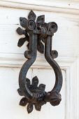 Vintage Black Metal Knocker On White Wooden Door