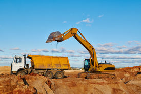 picture of boom-truck  - loader excavator machine loading dumper truck at sand quarry - JPG