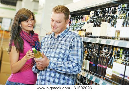 Young family couple choosing bottle ? wine in supermarket during weekly shopping