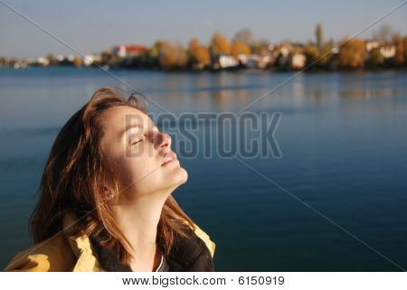 Young Woman With Face Turned To Sun With Beautiful Water Autumn Background