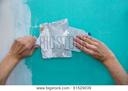 Plastering man hands with plaste on drywall plasterboard hydrophobic construction