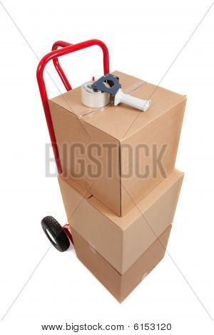 A Red Hand Truck On White With Boxes And A Tape Gun