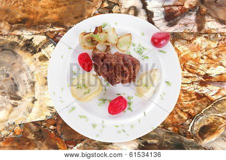 meat beef bourguignon in wine with artichoke and marinated vegetables on wooden table