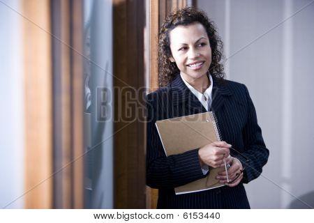 Confident Hispanic businesswoman standing in boardroom