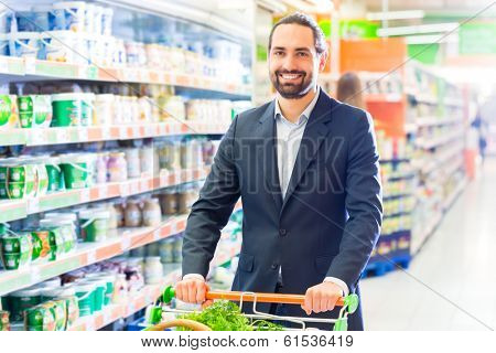 customer with pushcart in supermarket looking for groceries