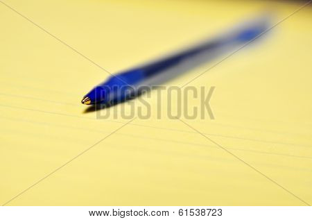 Closeup of blue ball point pen for business or education on legal pad