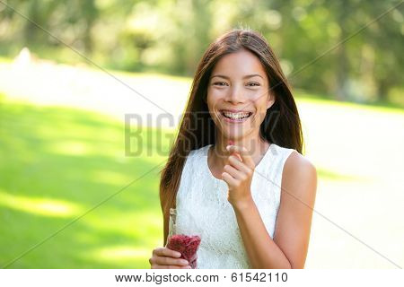 Woman eating goji berries healthy food snack outdoors in park. Healthy eating and lifestyle with beautiful mixed race Asian Caucasian female girl model. 20s