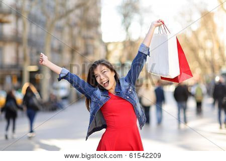 Happy shopping woman on La Rambla street Barcelona. Shopper girl holding shopping bags up excited outdoors on walking street. Mixed race Asian Caucasian female model in denim jacket. Spain.
