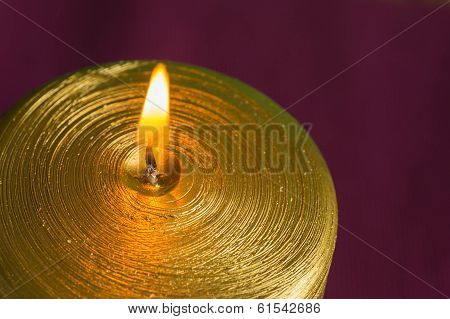 Gold Candle On A Claret Background Close Up