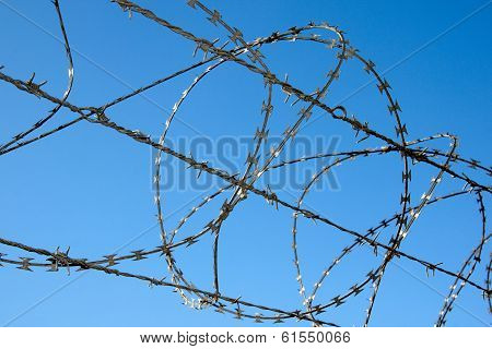 Close Up Of Razor Security Fence Against Blue Sky