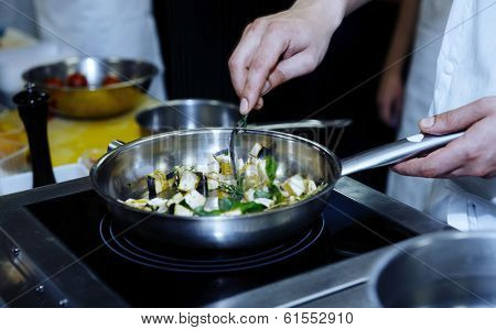 Chef is frying eggplant with herbs on professional kitchen, blue toned