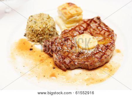 Rib eye steak with bulgur, butter and potato gratin, close-up
