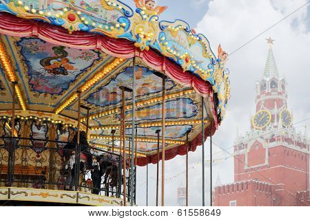 MOSCOW, RUSSIA - DEC 8, 2013: Children at carousel near Spasskaya tower during Christmas fair (area of fair is about 2 thousand square meters).