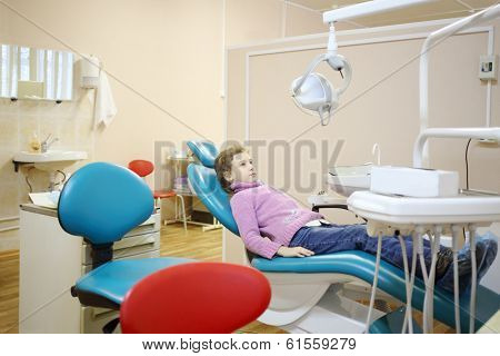 Pretty girl lies on dental chair in office, looks up and waits for doctor