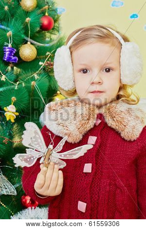 Half-length portrait of little girl dressed in knitted red coat and earmuffs with artificial butterfly in her hand