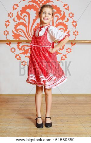 Smiling girl in red folk costume turns round near wall with pattern