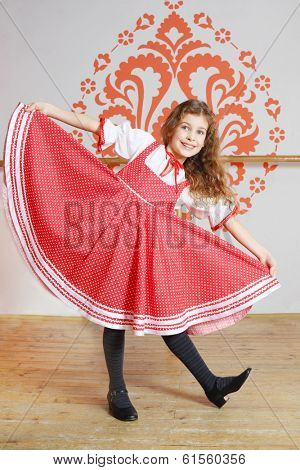 Smiling girl in red folk costume poses near wall with pattern