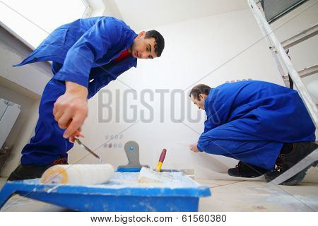 Workers in blue glue paint fiberglass and paint walls in new apartment