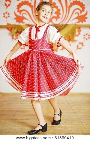 Beautiful girl in red folk costume dances near wall with pattern