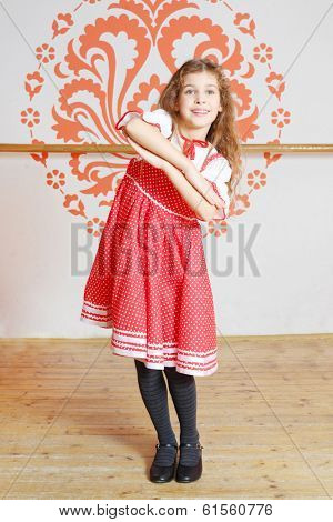 Smiling girl in red folk costume with performs near wall with pattern