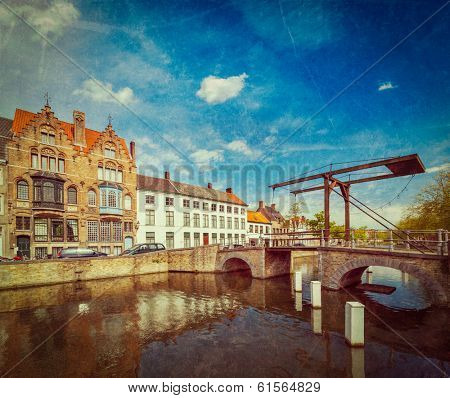 Vintage retro hipster style travel image of canal with old bridge. Bruges (Brugge), Belgium with grunge texture overlaid
