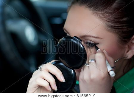The girl is doing makeup in the car