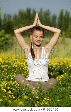 Portrait of a girl in the flower meadow. Woman meditating