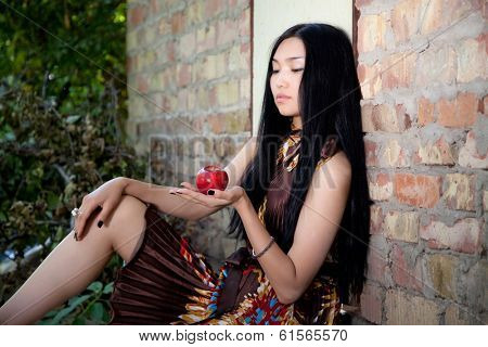Beautiful girl with a brick wall with apple