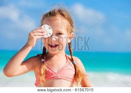 Adorable little girl at beach holding sand dollar
