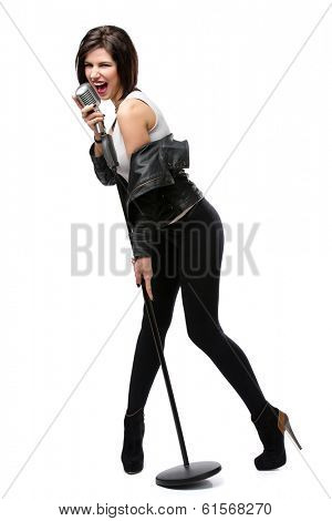 Full-length portrait of rock singer wearing leather jacket and handing static mic, isolated on white. Concept of rock music and rave