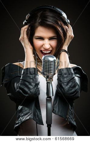 Half-length portrait of female rock musician with microphone and earphones. Concept of rock music and rave